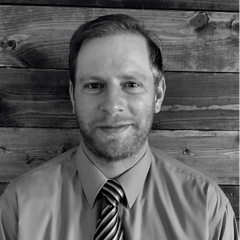 Image Description: Black and white photo of Jordan Vande Brake, Technical Manager at Separators, Inc. In a button-down shirt and striped tie